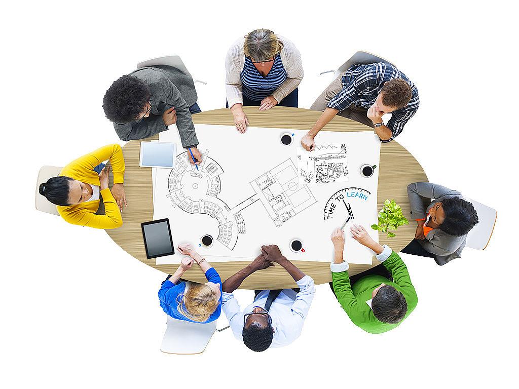 Bild: Personengruppe sitzt um Tisch