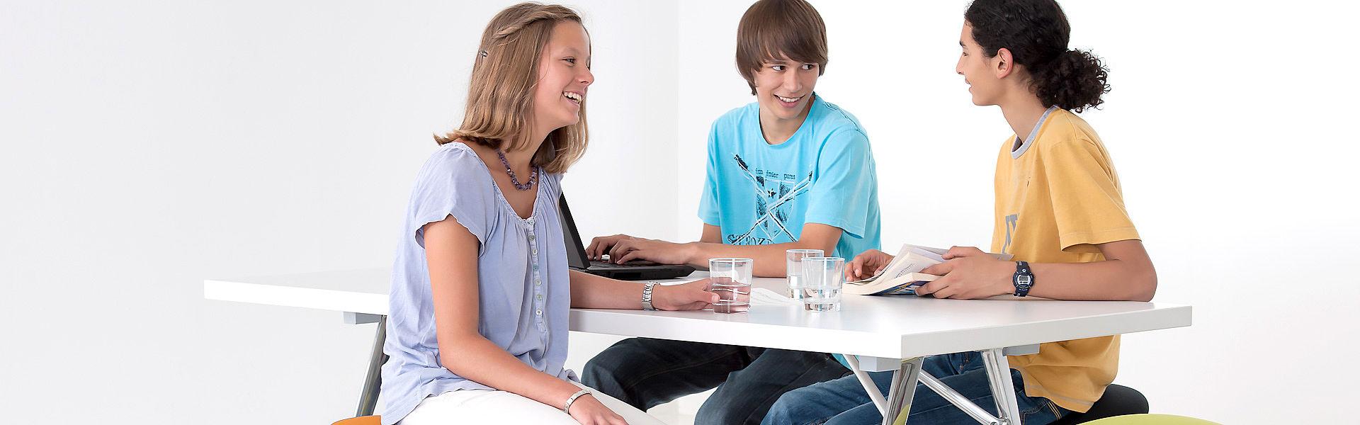 Bild: Jugendliche mit Laptop, Block an Tisch auf Hockern